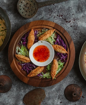 Vue de dessus khinkali rôti et servi avec des herbes et une sauce chili.