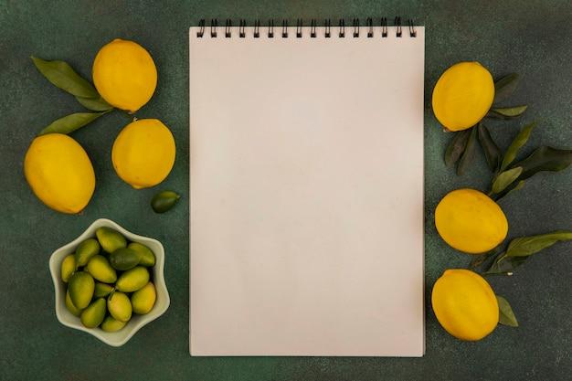 Vue de dessus des kinkans frais sur un bol avec des citrons isolés sur une surface verte avec espace copie