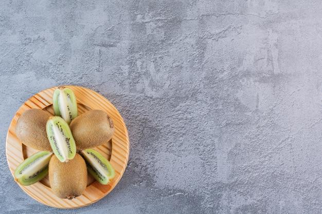 Vue de dessus des kiwis entiers ou tranchés sur plaque en bois.