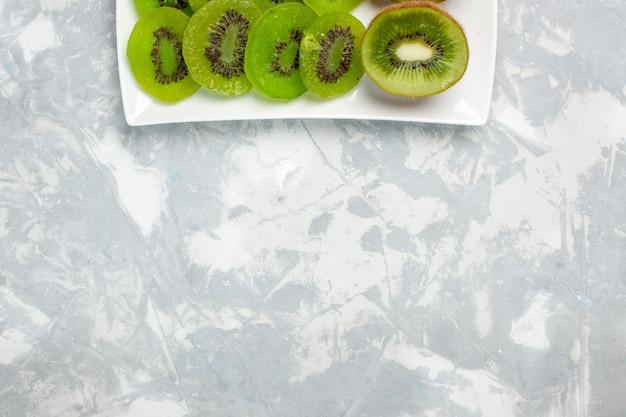 Vue de dessus des kiwis frais tranchés à l'intérieur de la plaque sur fond blanc