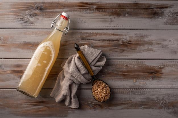 Vue de dessus kvass de seigle léger traditionnel russe en bouteille et serviette en lin sur bois