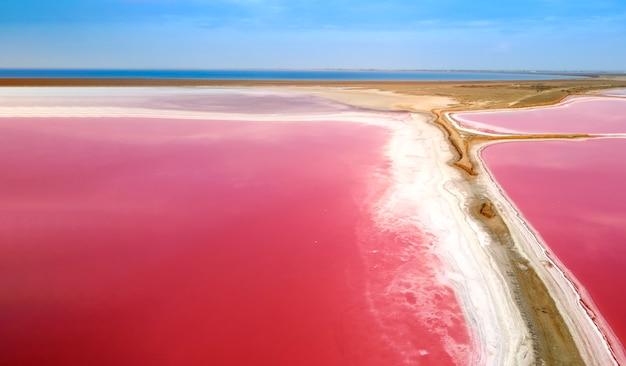 Vue de dessus d'un lac rose. la rive étroite séparant le lac et la baie de la mer.
