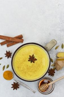 Vue de dessus de latte au curcuma. lait doré dans une tasse avec de l'anis étoilé et des épices autour.