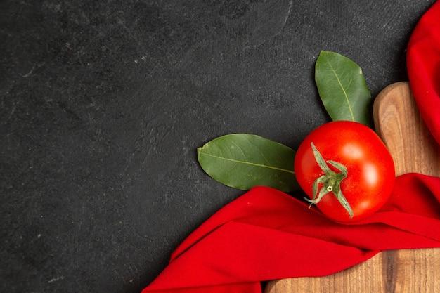 Vue de dessus un laurier de tomate laisse une serviette rouge et une planche à découper sur un sol sombre