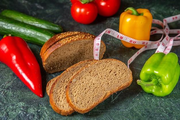Vue de dessus des légumes biologiques frais entiers et mètre de tranches de pain noir sur la surface des couleurs de mélange