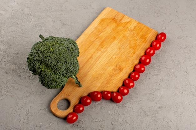 Vue de dessus légumes brocoli vert frais et tomates cerises rouges sur le bureau gris