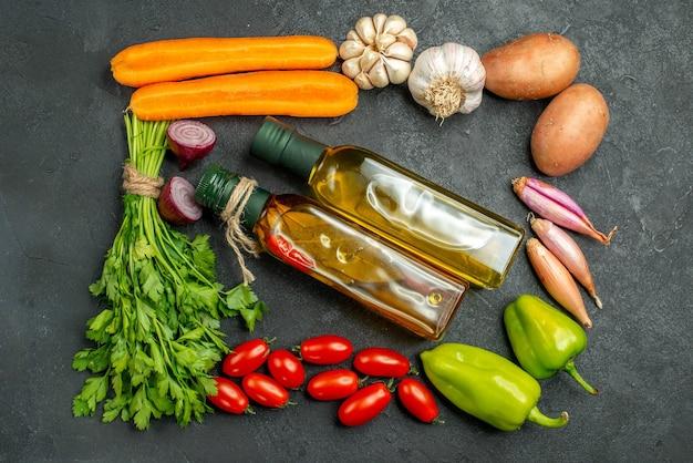 Vue de dessus des légumes en carré et avec des bouteilles d'huile au centre sur fond gris foncé