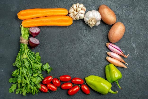Vue de dessus des légumes en carré et avec place libre pour votre texte au centre sur fond gris foncé