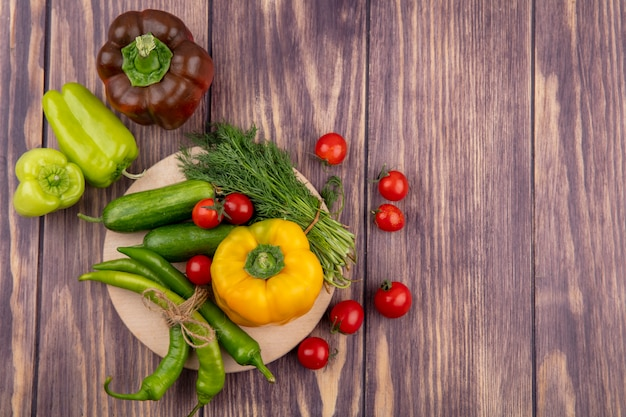 Vue de dessus des légumes comme l'aneth de tomate poivron concombre sur une planche à découper et sur une surface en bois