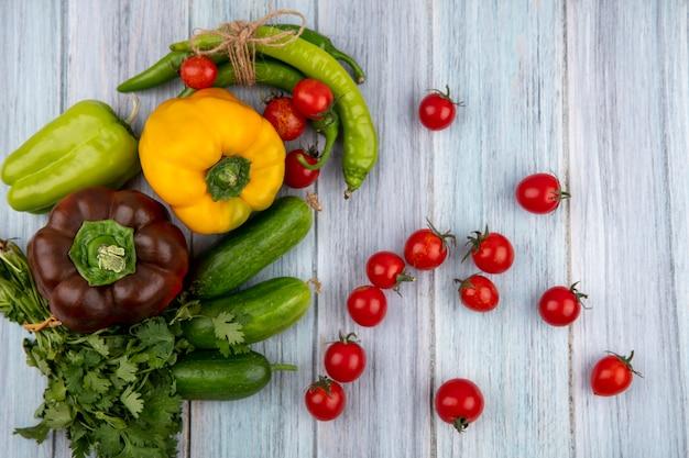 Vue de dessus des légumes comme concombre tomate poivre coriandre sur surface en bois