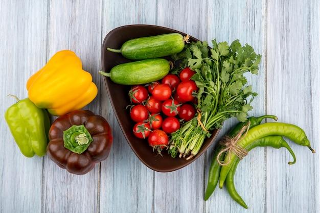 Vue de dessus des légumes comme concombre tomate tas de coriandre dans un bol avec des poivrons sur une surface en bois