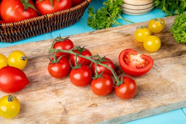 Vue de dessus des légumes comme la coriandre tomate sur une planche à découper avec des tomates concasseur à l'ail sur bleu