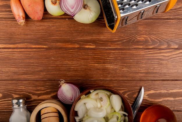 Vue de dessus des légumes comme différents types de pommes de terre oignons coupés et tranchés entiers avec couteau à beurre de sel et râpe sur fond de bois avec copie espace