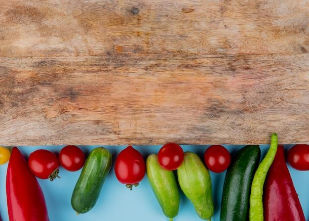 Vue de dessus des légumes comme du concombre de tomate au poivre avec planche à découper sur la surface bleue