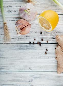 Vue de dessus des légumes comme l'oignon échalote au gingembre citron avec des grains de poivre noir sur fond de bois avec copie espace