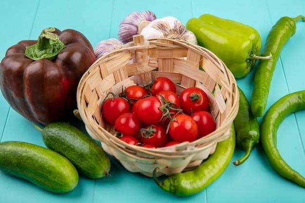 Vue de dessus des légumes comme panier de tomate et concombre poivron ail sur surface bleue
