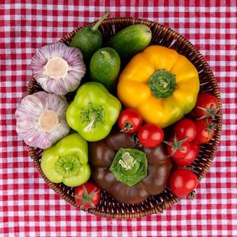 Vue de dessus des légumes comme poivron concombre tomate ail dans le panier sur la surface en tissu à carreaux
