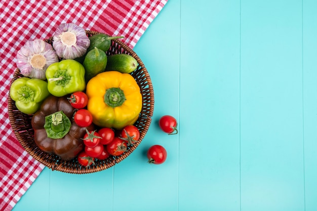 Vue de dessus des légumes comme poivron concombre tomate ail dans le panier sur tissu à carreaux et sur la surface bleue
