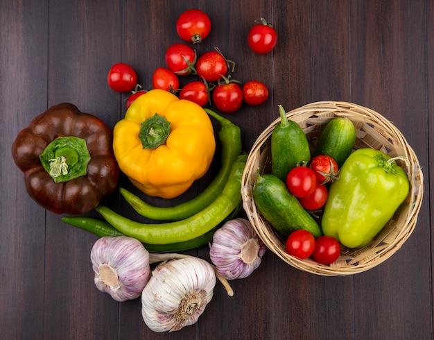 Vue de dessus des légumes comme poivron tomate concombre ail dans le panier et sur la surface en bois