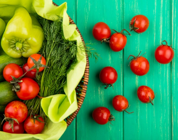Vue de dessus des légumes comme poivron tomate concombre aneth dans le panier sur la surface verte