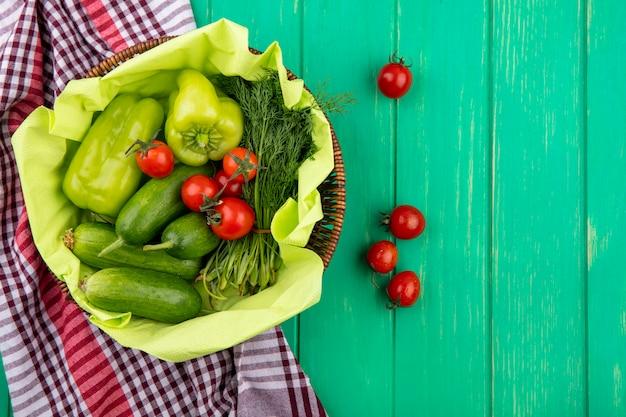 Vue de dessus des légumes comme poivron tomate concombre aneth dans le panier sur tissu à carreaux et surface verte