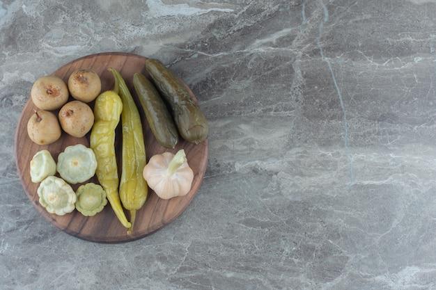 Vue de dessus des légumes en conserve sur planche de bois.
