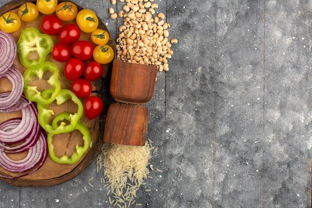 Vue de dessus des légumes de couleur oignons tranchés poivron vert et tomates sur le bureau brun et gris