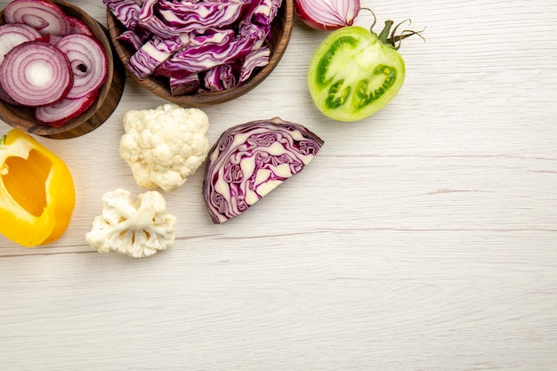 Vue de dessus légumes coupés chou rouge tomate verte citrouille oignon rouge poivron chou-fleur citron dans des bols en bois sur une surface en bois blanc avec copie place