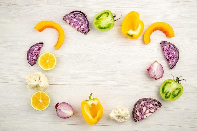 Vue de dessus légumes coupés chou rouge tomate verte citrouille oignon rouge poivron jaune chou-fleur citron sur surface en bois blanc place libre