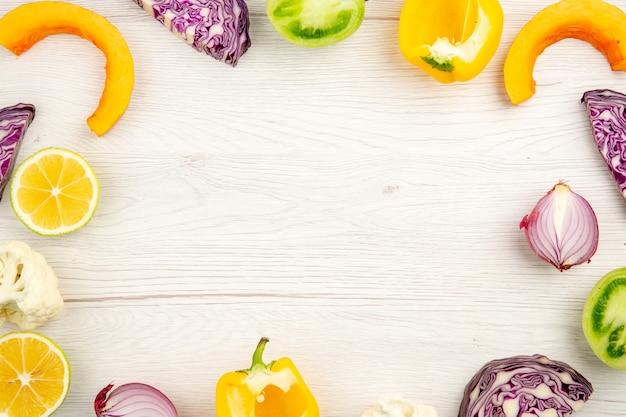 Vue de dessus légumes coupés chou rouge tomate verte citrouille oignon rouge poivron jaune chou-fleur citron sur une surface en bois blanche avec place libre