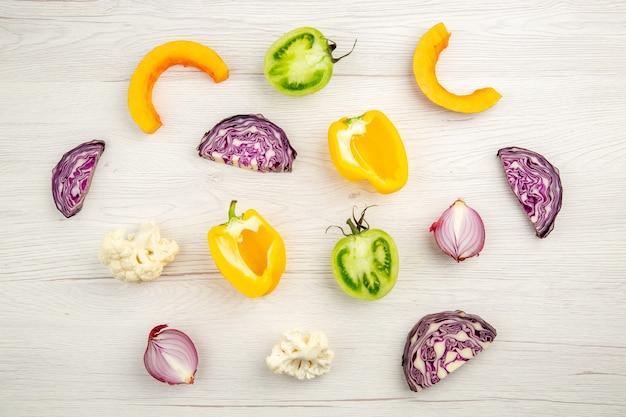 Vue de dessus légumes coupés chou rouge tomate verte citrouille oignon rouge poivron jaune chou-fleur sur la surface en bois blanc