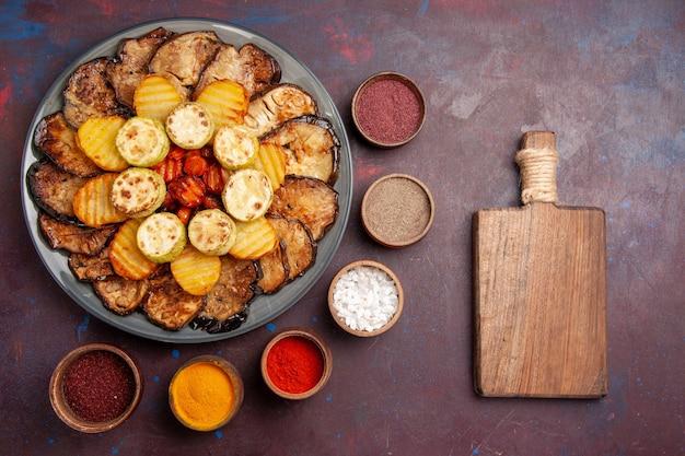 Vue de dessus, légumes cuits au four, pommes de terre et aubergines avec assaisonnements sur l'espace sombre