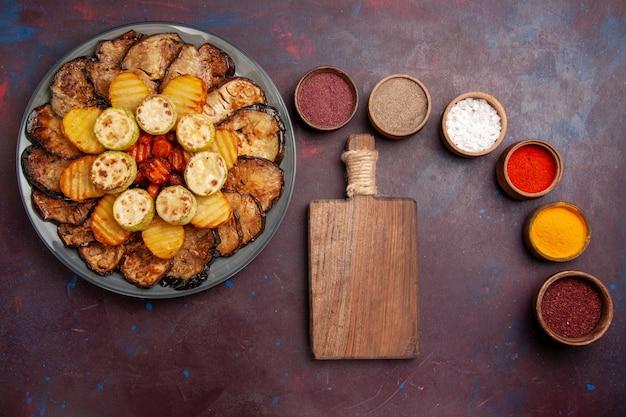 Vue de dessus légumes cuits au four, pommes de terre et aubergines avec différents assaisonnements sur un espace sombre