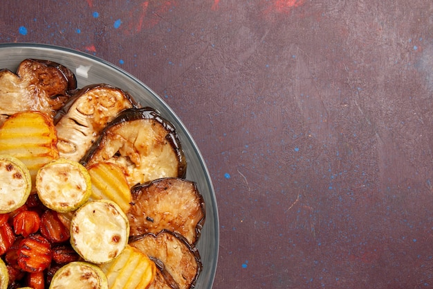Vue de dessus, légumes cuits au four, pommes de terre et aubergines fraîchement sorties du four sur un espace sombre