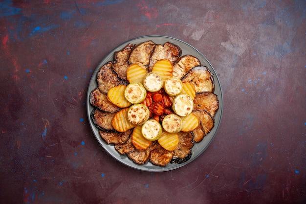 Vue de dessus légumes cuits au four pommes de terre et aubergines à l'intérieur de la plaque sur l'espace sombre