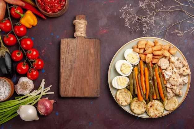 Vue de dessus légumes cuits avec repas aux œufs et légumes frais sur un espace sombre