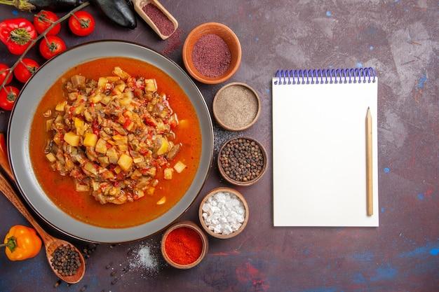 Vue de dessus légumes cuits tranchés avec sauce et assaisonnements sur fond sombre sauce repas repas dîner soupe légumes