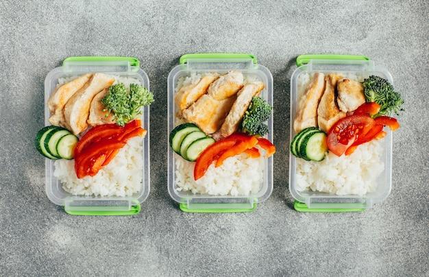 Vue de dessus des légumes, du riz, de la viande dans des bols en plastique sur fond gris clair