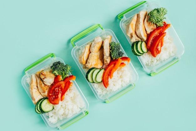 Vue de dessus des légumes, du riz, de la viande dans des bols en plastique sur fond vert clair