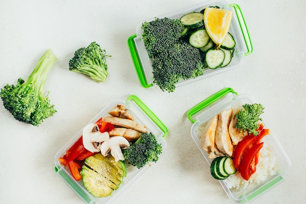 Vue de dessus des légumes, du riz, de la viande dans des bols en plastique sur une surface blanche claire