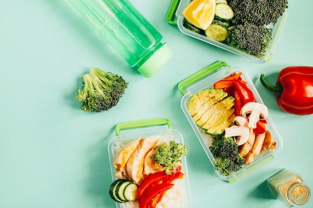 Vue de dessus des légumes, du riz, de la viande dans des bols en plastique sur une surface vert clair