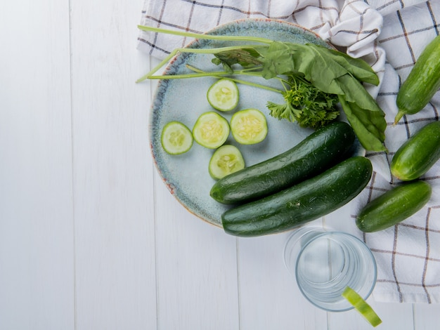 Vue de dessus des légumes entiers et en tranches de coriandre aux épinards de concombre avec des concombres sur un chiffon et de l'eau détox sur une surface en bois avec copie espace