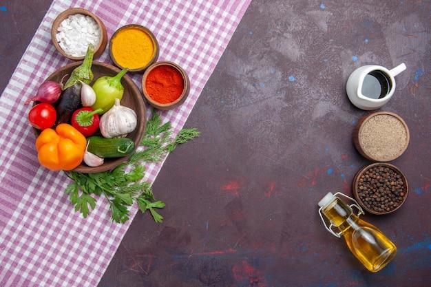 Vue de dessus des légumes frais avec des assaisonnements sur la surface sombre salade mûre déjeuner santé