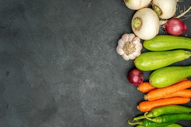 Vue de dessus des légumes frais bordés sur fond sombre