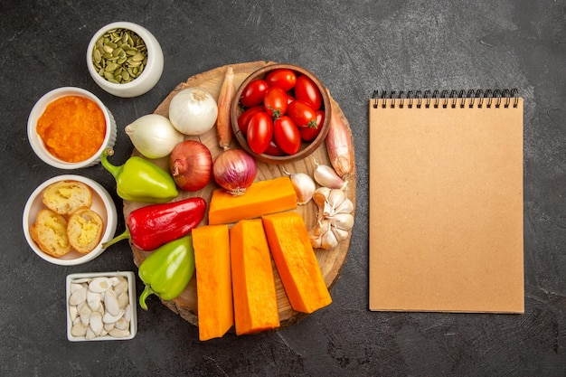 Vue de dessus des légumes frais avec de la citrouille et des graines sur la couleur du repas mûr de la salade de fond sombre