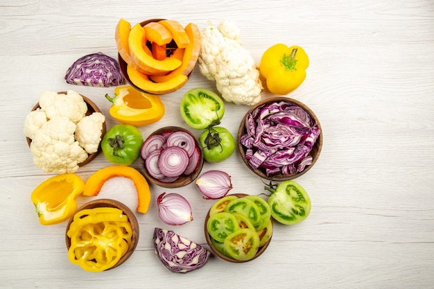 Vue de dessus légumes frais coupés tomates vertes chou rouge oignon potiron chou-fleur poivron jaune dans des bols sur l'espace libre de surface en bois blanc
