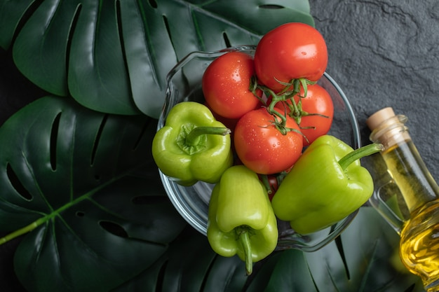 Vue de dessus des légumes frais dans un bol en verre et une bouteille d'huile.