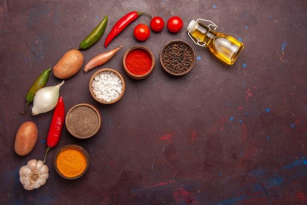 Vue de dessus des légumes frais avec différents assaisonnements sur l'espace sombre