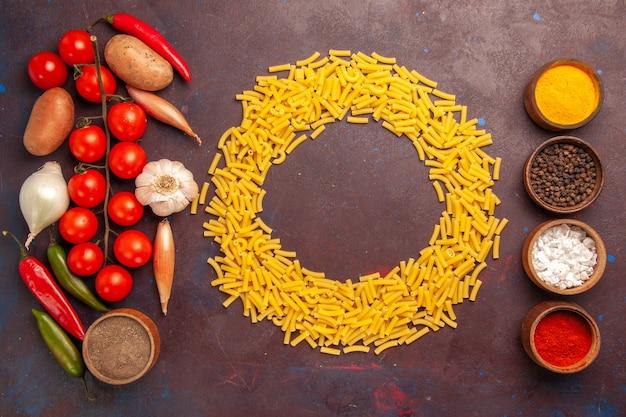 Vue de dessus des légumes frais avec différents assaisonnements et pâtes sur l'espace sombre