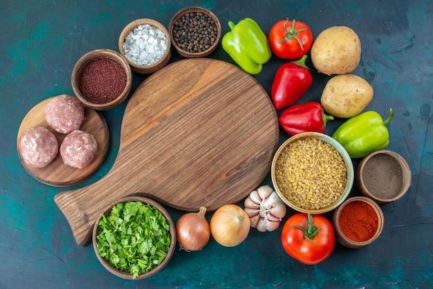 Vue de dessus des légumes frais avec différents assaisonnements et verts sur un bureau bleu foncé